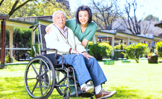 senior man on a wheelchair smiling with caregiver