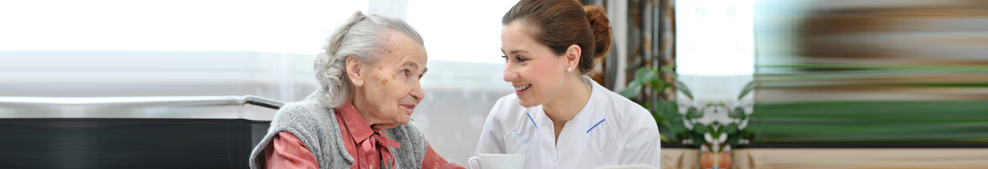female caregiver and senior woman smiling while holding the cup